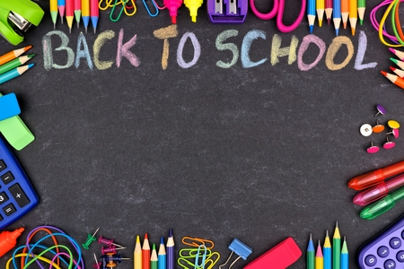 Escuela de suministros de marco con la espalda a la escuela escrita en tiza de colores contra un fondo de pizarra Foto de archivo - 82239633