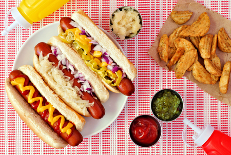 Hot dogs with assorted toppings and potato wedges, above scene on a red and white cloth