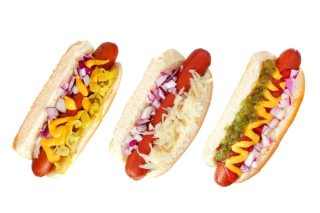 Tres perros calientes con un surtido de coberturas, vista superior aislado en un fondo blanco Foto de archivo - 83150935