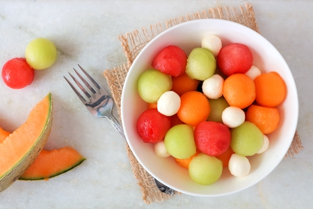 Summer fruit salad with watermelon, honeydew, cantaloupe and cheese, top view on a marble background