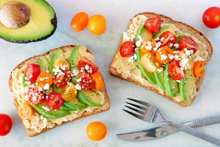 Avocado toasts with hummus and tomatoes, overhead view on white marble background