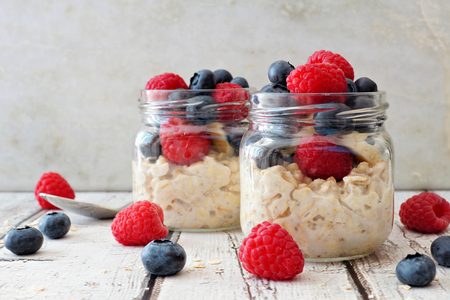 Overnight oats with fresh blueberries and raspberries in jars on a rustic white wood background Stockfoto