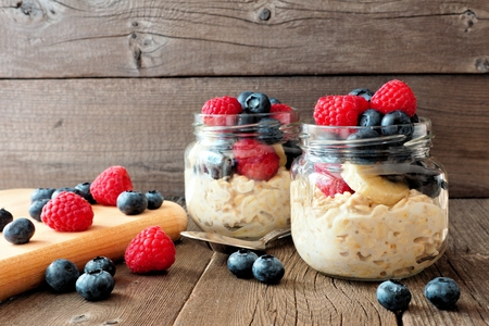 Overnight oats with fresh blueberries and raspberries in jars on a rustic wood background Stock Photo