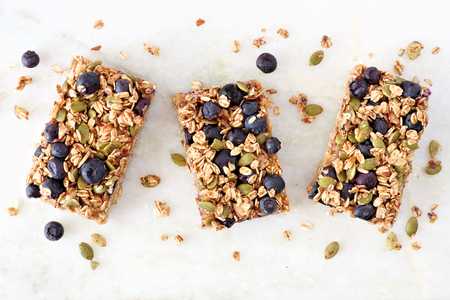 Superfood breakfast bars with oats and blueberries, above view on white marble background Foto de archivo