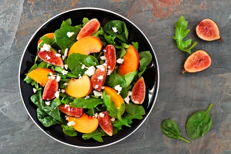 Autumn salad of arugula, spinach figs and goat cheese in a black plate, above view on a slate background