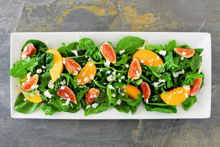 Autumn salad of arugula, spinach, figs and goat cheese in a white rectangular plate, overhead view on slate