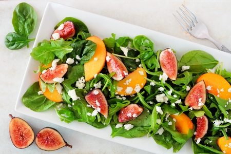 Autumn salad of arugula, spinach, figs and goat cheese in a white rectangular plate, overhead scene on marble Stock Photo