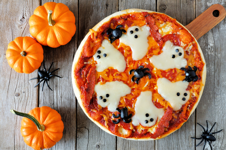 Halloween pizza with ghosts and spiders, above scene with decor on a rustic wood background