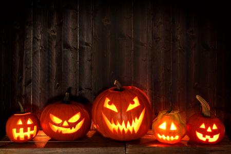 Grupo de Halloween Jack o linternas en la noche con un fondo rústico de madera oscura