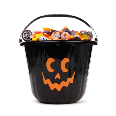 Black Halloween Jack o Lantern candy collector filled with candy over a white background Foto de archivo