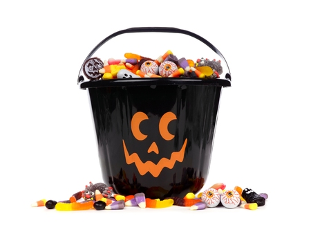 sucker: Black Halloween Jack o Lantern candy collector with scattered candy over a white background