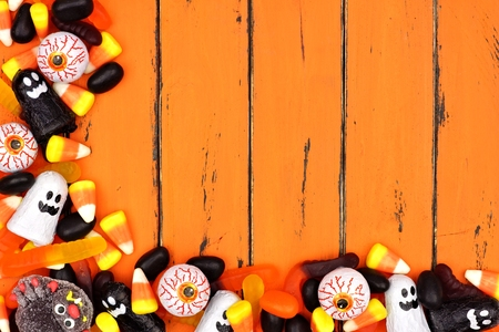 Halloween candy corner border over an old orange wood background