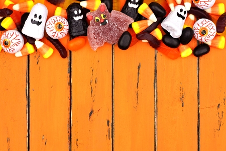 Halloween candy top border over an old orange wood background