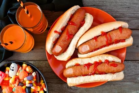 핫도그 손가락, 음료 및 사탕, 위의 나무 배경 할로윈 식사 현장 스톡 콘텐츠
