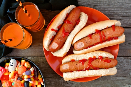 Halloween meal scene with hot dog fingers, drinks and candy, above view a wood background Reklamní fotografie - 85159750