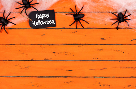 Happy Halloween tag with spider web top border on an old orange wood background