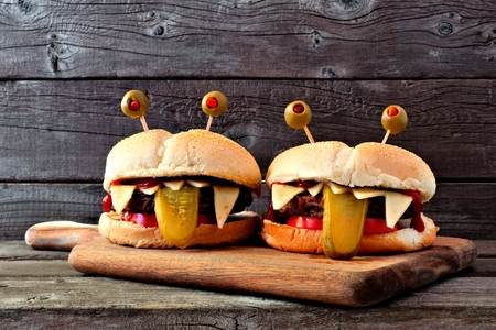 Halloween monster hamburgers on a paddle board against an old wood background