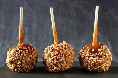 暗いスレートの背景にナッツを持つ3つのお祝いキャラメルりんご