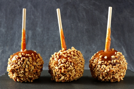 Three festive caramel apples with nuts against a dark slate background