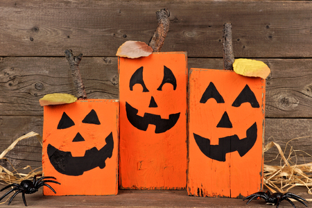 Rustic wooden Halloween Jack o Lanterns against an aged wood background