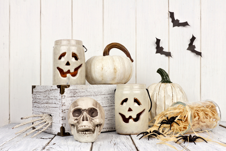 Rustic white Halloween decor still life against a white wood background