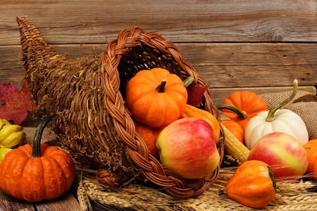 Thanksgiving cornucopia filled with pumpkins and fruit against a rustic wooden background