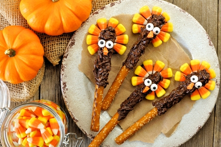 Funny Thanksgiving turkey pretzel rods with candy corn, overhead scene on old wood