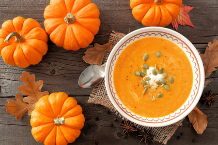 butternut: Creamy pumpkin soup, rustic autumn table scene, overhead view on aged wood Stock Photo