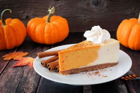 Slice of pumpkin cheesecake with whipped cream on a dark rustic wood background