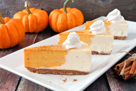 Three slices of pumpkin cheesecake with whipped cream on a white serving plate