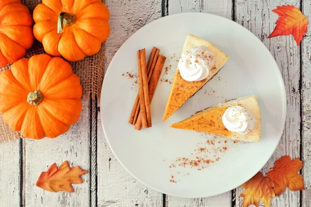 Plate with two slices of pumpkin cheesecake with whipped cream, overhead view on a white wood background Foto de archivo