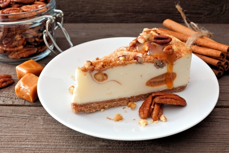 Slice of pecan caramel cheesecake on plate with a rustic wood background Foto de archivo