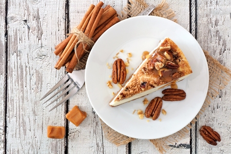Slice of pecan caramel cheesecake, top view on a rustic white wood background