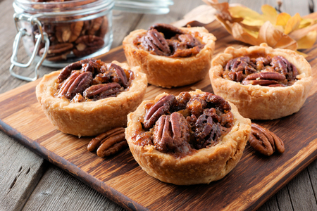 Mini pecan pie tarts, close up scene on a wooden server against a rustic wood background