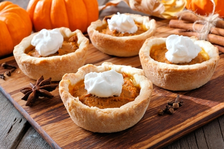 Mini pumpkin pie tarts, close up scene on a wooden server against a rustic wood background