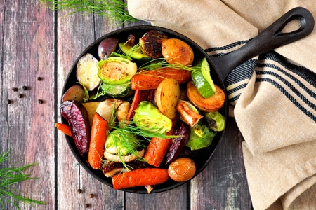 Cast iron skillet of roasted autumn vegetables, overhead scene on a rustic wood background