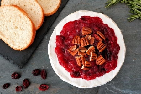 Brie appetizer topped with cranberries and pecans, overhead scene on slate background