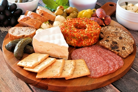 Appetizer platter with an assortment of cheeses, crackers, meats and snacks close up with a wood background
