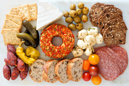 Appetizer spread with an assortment of cheeses, crackers, meats and snacks over a marble background