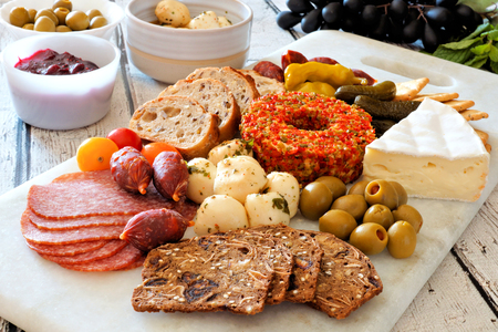 Appetizer platter with an assortment of cheeses, crackers, meats and snacks on a marble server Stock Photo