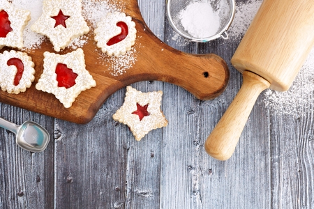Christmas baking overhead scene on a wooden background with Linzer jam cookies