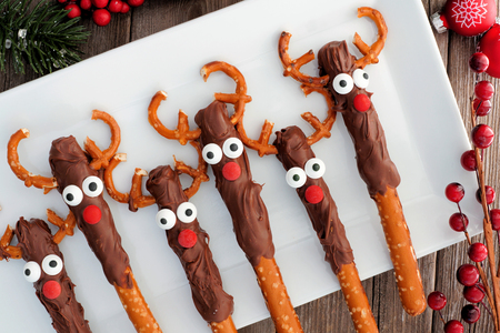 Cute Christmas reindeer chocolate dipped pretzel rods, above on a white serving plate
