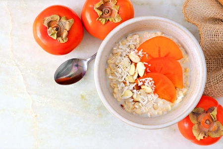 Breakfast oatmeal with persimmons, almonds and coconut, above scene on a marble background. Corner orientation with copy space. Stock Photo