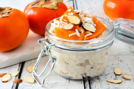 Overnight breakfast oatmeal with persimmons, almonds and coconut. Side view table scene on a rustic wooden background Stock Photo