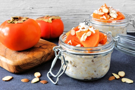 Overnight breakfast oatmeal with persimmons, almonds and coconut. Side view table scene on a dark background