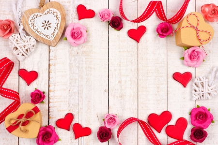 Valentines Day frame of hearts, flowers, gifts and decor against a rustic white wood background with copy space.