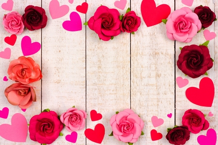 Valentines Day frame of red and pink paper hearts and roses against a rustic white wood background with copy space. Banco de Imagens