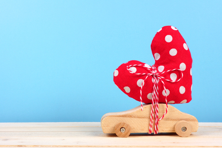 Wooden toy car carrying homemade heart gift against a blue background. Valentines Day or love concept.