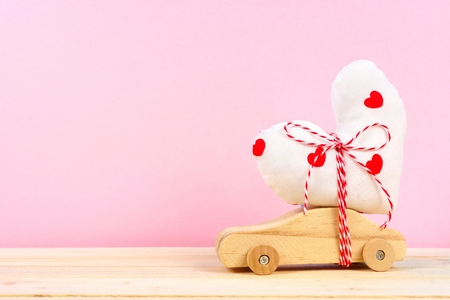 Wooden toy car carrying homemade heart gift against a pink background. Valentines Day or love concept.
