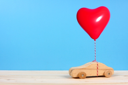 Wooden toy car with a red heart balloon against a blue background. Valentines Day or love concept. Reklamní fotografie
